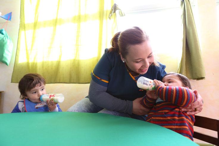 Adulta dando alimentación a un niño.